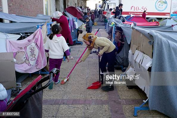 A migrant girl from Syria sweeps in front of improvised shelter outside a passenger terminal at the port of Piraeus on March 2 2016 in Athens Greece...