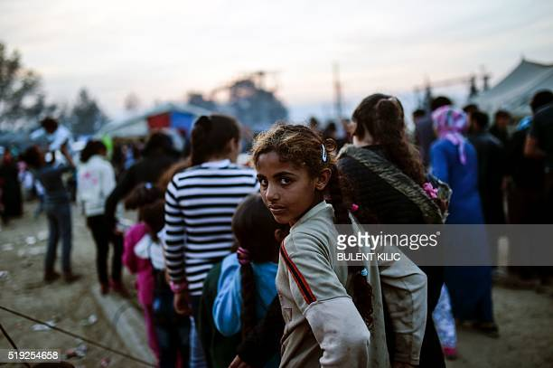 A migrant girl looks on as she waits for a food distribution at the makeshift camp at the GreekMacedonian border village of Idomeni on April 5 2016 A...