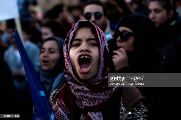 TOPSHOT A migrant girl shouts a slogan during a demonstration by Greek antifascist groups against the war in Syria and the European Union's stance on...
