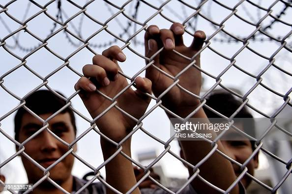 A migrant grabs a razor wire topped fence as the Greek prime minister visits a refugee and migrant registration camp in Mytilene on the Greek island...