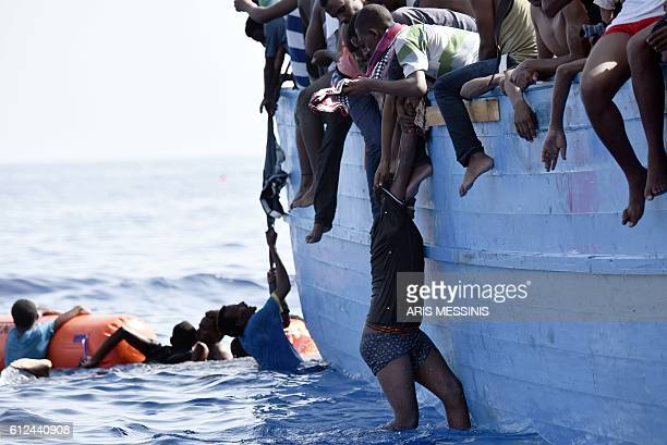 A migrant hangs from a boat as they wait to be rescued as they drift in the Mediterranean Sea some 12 nautical miles north of Libya on October 4 2016...