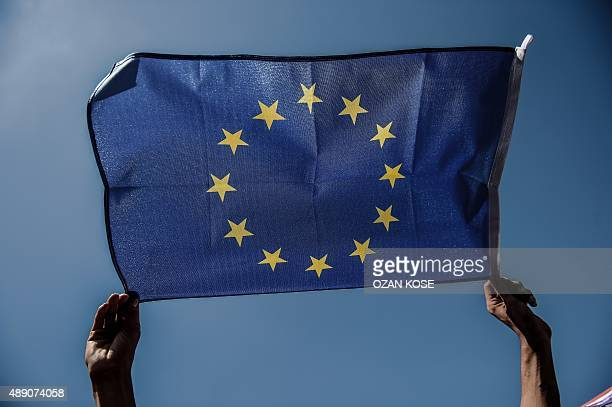 A migrant holds a European Union flag as migrants and refugees stage a demonstration at Istanbul's Esenler Bus Terminal on September 19 2015 after...