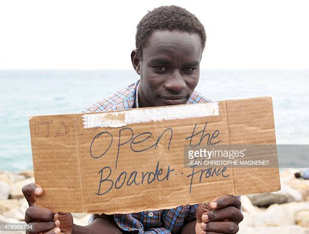 A migrant holds a placard reading 'Open the border France' as he waits with other migrants at the border between Italy and France in the city of...