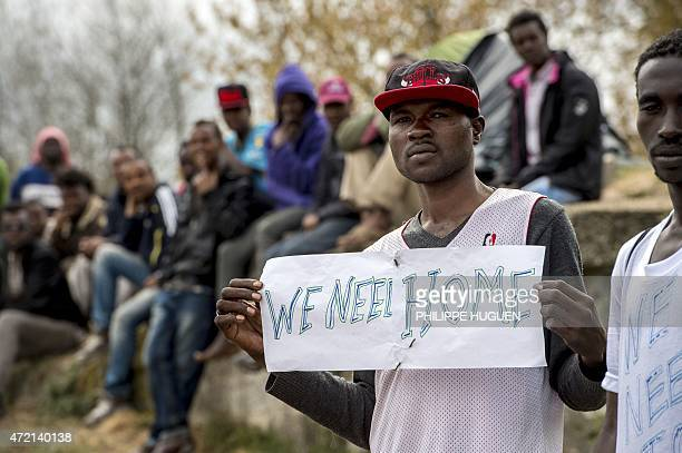 A migrant holds a sign reading 'We need a home' during a visit by the French interior minister to their shelter in Calais northern France on May 4...