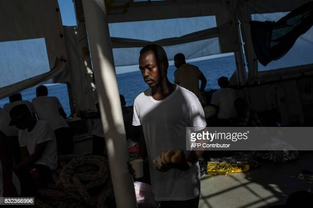 TOPSHOT A migrant holds his meal on the deck of the Aquarius rescue ship run by NGO SOS Mediterranee and Medecins Sans Frontieres after the transfer...