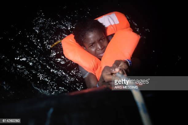 TOPSHOT A migrant holds onto a rope during a rescue operation some eight nautical miles off Libya's Mediterranean coastline on October 12 2016 A...