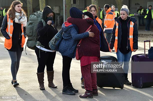 A migrant hugs with a volunteer as she leaves the 'Jules Ferry' reception centre next to the recently demolished 'Jungle' migrant camp after a...