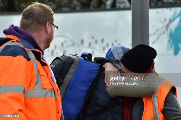 A migrant hugs with a volunteer of the association 'La Vie Active' as she leaves the 'Jules Ferry' reception centre next to the recently demolished...