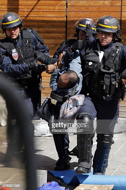 A migrant is arrested by the police during an evacuation operation on June 8 2015 in front of the Vaclav Havel library rue Pajol in the 18th...