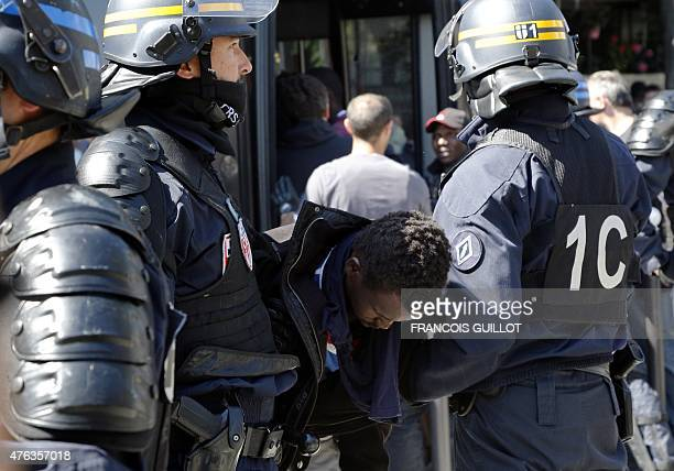 A migrant is arrested by the police on June 8 2015 in front of the Vaclav Havel library rue Pajol in the 18th arrondissement of Paris Around 30...