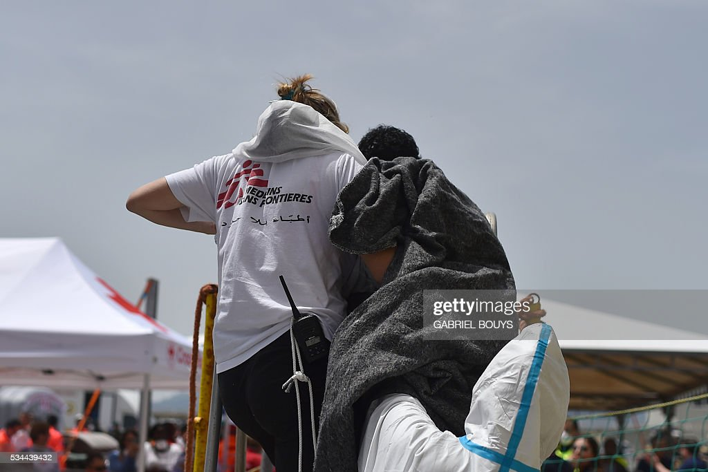 A migrant is helped by a member of French NGO Doctors Without Borders (MSF) to disembark from rescue ship 'Aquarius' as they arrive in the port of Cagliari, Sardinia, on May 26, 2016, two days after being rescued near the Libyan coasts. The Aquarius is a former North Atlantic fisheries protection ship now used by humanitarians SOS Mediterranee and Medecins Sans Frontieres (Doctors without Borders) which patrols to rescue migrants and refugees trying to reach Europe crossing the Mediterranean sea aboard rubber boats or old fishing boat. / AFP / GABRIEL