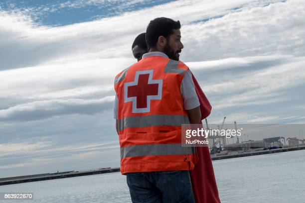 A migrant is helped by a Red Cross member after arriving on a Spanish coast guard vessel into the southern Spanish port of Malaga on October 20 2017...