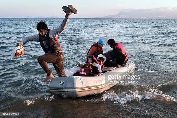 A migrant jumps off a small dinghy after arriving to the shores of the Greek island of Kos from Turkey on August 18 2015 Authorities on the island of...