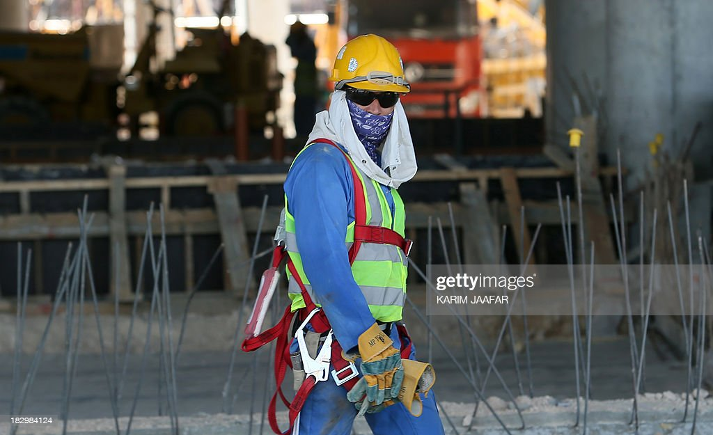 A migrant labourer walks as he works on a construction site on October 3 2013 in Doha in Qatar Qatar the 2022 World Cup host is under fire over...