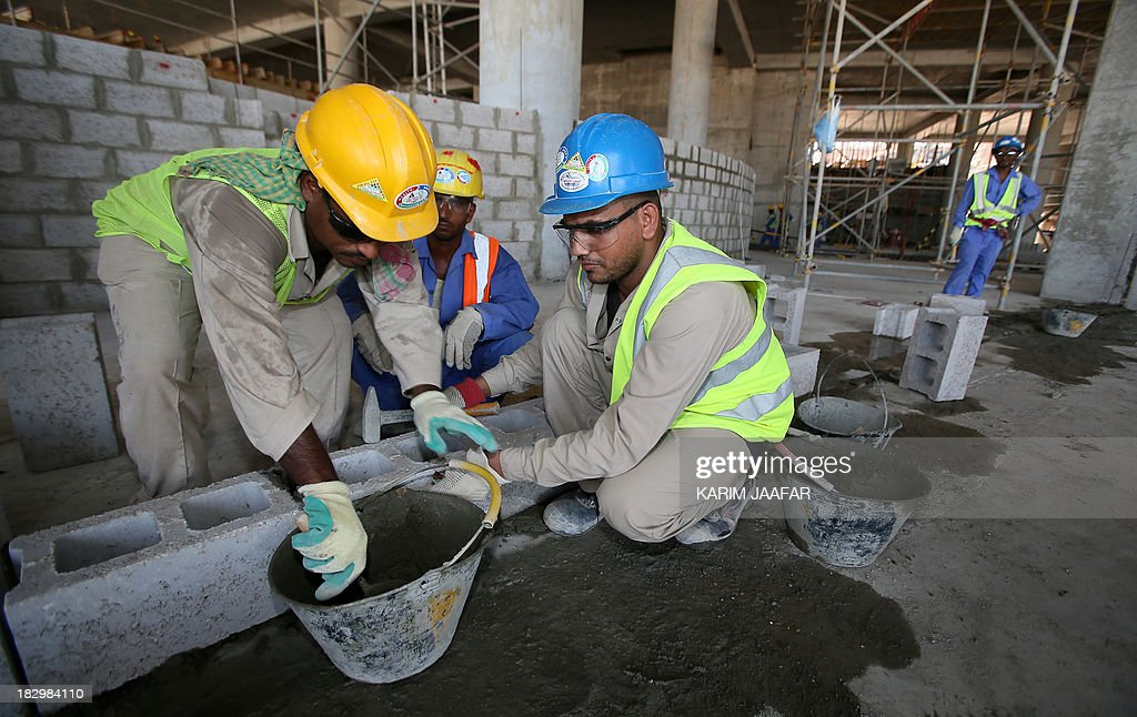Migrant labourers work on a construction site on October 3, 2013 in Doha in Qatar. Qatar, the 2022 World Cup host is under fire over claims of using forced labour. Global football's governing body FIFA kicked off a crunch meeting behind closed doors, amid claims of rights abuses by Qatar and wrangling over plans to hold the tournament in the winter.