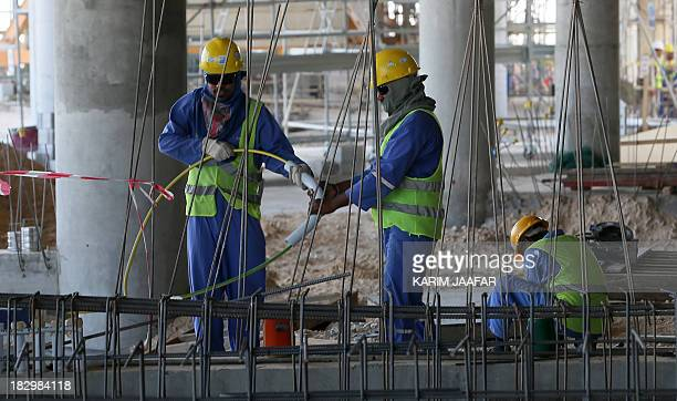 Migrant labourers work on a construction site on October 3 2013 in Doha in Qatar Qatar the 2022 World Cup host is under fire over claims of using...