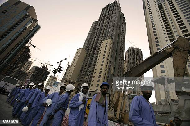Migrant labourers working in the construction industry wait for their buses at the end of their working day on May 1 2006 in Dubai United Arab...