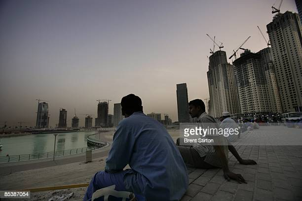 Migrant labourers working in the construction industry wait to go back to their camp by bus at the end of the working day in the Dubai Marina area on...