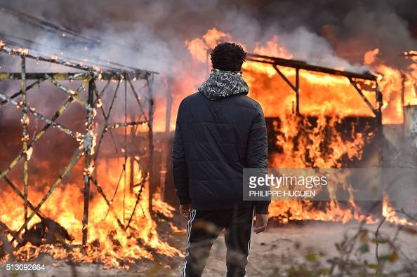 A migrant looks at shacks burning during the dismantling of half of the 'Jungle' migrant camp in the French northern port city of Calais on February...