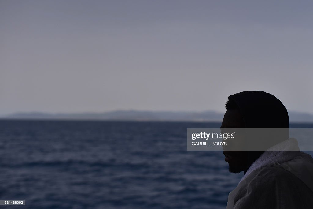 A migrant looks at the Sardinia island from rescue ship 'Aquarius' prior to arrive in the port of Cagliari, on May 26, 2016, two days after being rescued near the Libyan coasts. The Aquarius is a former North Atlantic fisheries protection ship now used by humanitarians SOS Mediterranee and Medecins Sans Frontieres (Doctors without Borders) which patrols to rescue migrants and refugees trying to reach Europe crossing the Mediterranean sea aboard rubber boats or old fishing boat. / AFP / GABRIEL