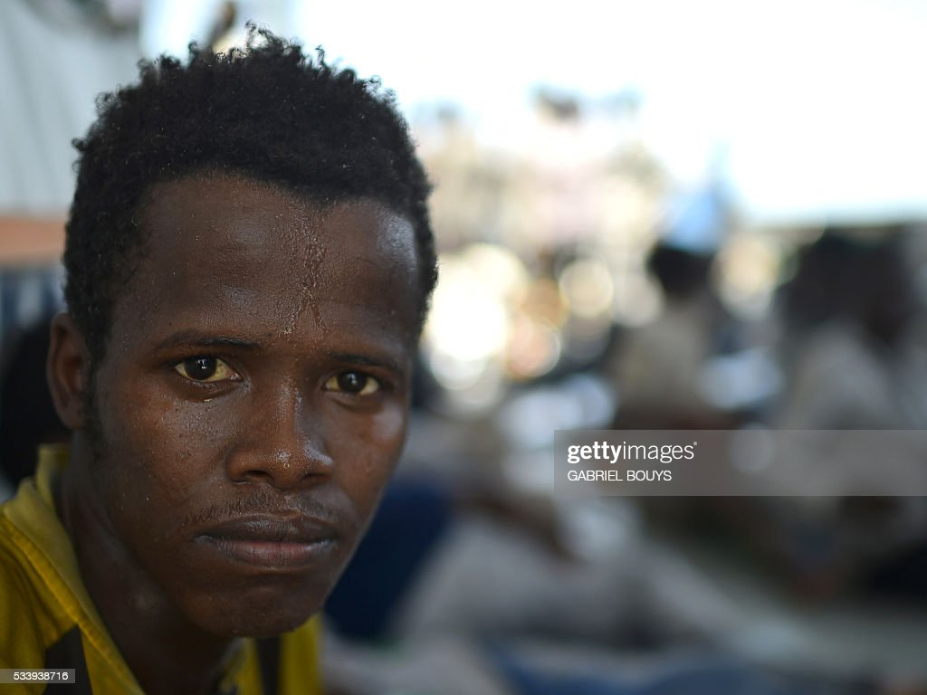 A migrant looks on after being rescued during an operation at sea with the Aquarius, a former North Atlantic fisheries protection ship now used by humanitarians SOS Mediterranee and Medecins Sans Frontieres (Doctors without Borders), on May 24, 2016 in the Mediterranean sea in front of the Libyan coast. / AFP / GABRIEL