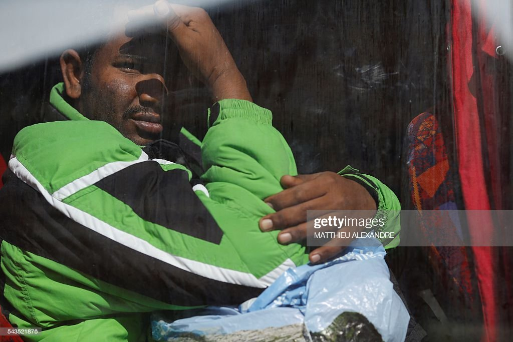 A migrant looks through the window of a bus as French Gendarms proceed to the evacuation of migrants near the Pajol hall on June 29, 2016 in Paris. The police started early on June 29, 2016, the evacuation of several hundreds of migrants, from a camp at the former SNCF Hall 'Pajol'. / AFP / MATTHIEU