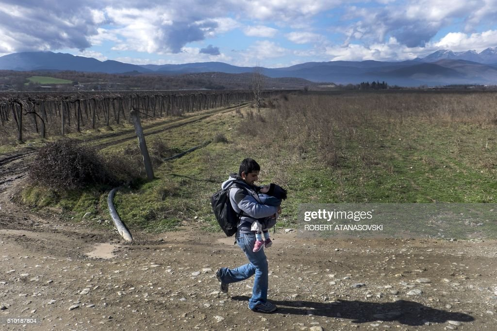 A migrant man carrying a child crosses the Greek-Macedonian border near the town of Gevgelija, on February 14, 2016. Dutch Foreign minister Bert Koenders on February 14 spent an hour in a Vinojug recipient center near Gevgelija talking with migrants, children, UNICEF and Red Cross representatives, police and others members that are taking care of migrants that are heading to the EU from devastated homes in Syria, Afghanistan and Iraq. / AFP / Robert ATANASOVSKI