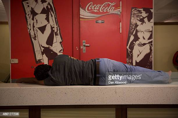 A migrant man sleeps on a counter onboard a Blue Star ferry during a ten hour journey from the island of Kos to the Greek mainland port of Piraeus on...