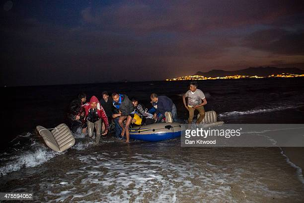 Migrant men arrive on the beach in a dinghy at dawn after making their way from Turkey on June 02 2015 in Kos Greece Migrants are continuing to...