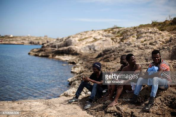 Migrant men from Nigeria relax by the sea on April 22 2015 in Lampedusa Italy Migrants continue to arrive on the island of Lampedusa from North...