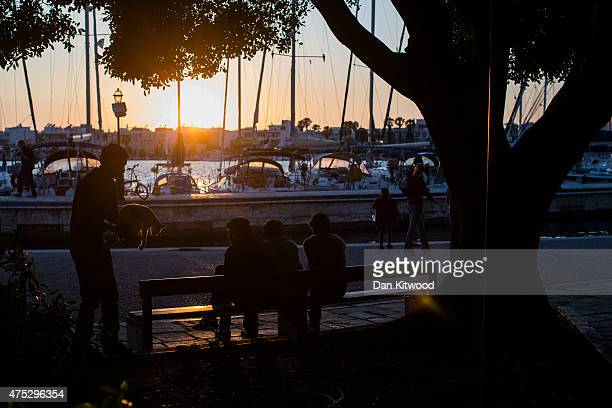Migrant men sit on a bench overlooking the harbour at sunset on May 30 2015 in Kos Greece Many migrants are continuing to arrive on the Greek Island...