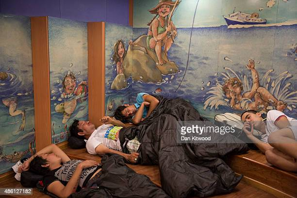 Migrant men sleep under a mural onboard a Blue Star ferry during a ten hour journey from the island of Kos to the Greek mainland port of Piraeus on...