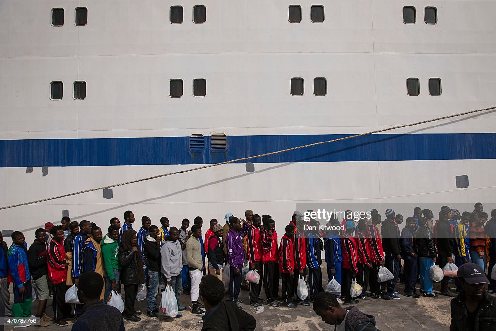 Migrant men wait in line to board a ship bound for Sicily on April 23 2015 in Lampedusa Italy It is expected that EU leaders in Brussels are to agree...