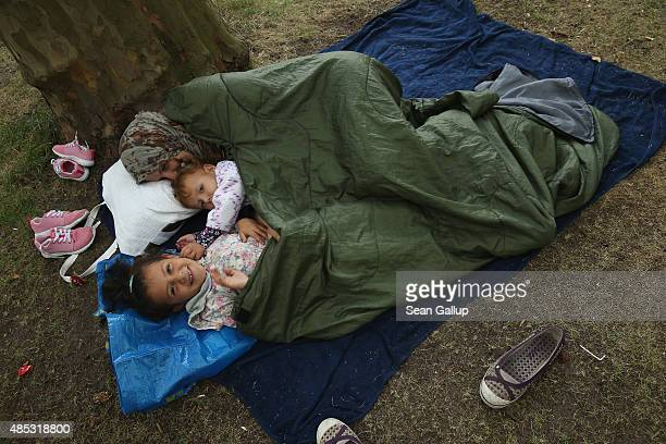 A migrant mother and children from Syria seeking asylum in Germany lie huddled in blankets outside the Central Registration Office for Asylum Seekers...