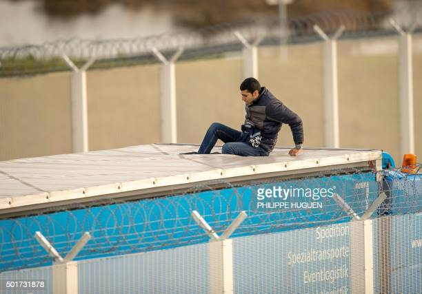 TOPSHOT A migrant or refugee enters the trailer of a truck after having cut the tarpaulin roof on December 17 2015 on the site of the Eurotunnel in...