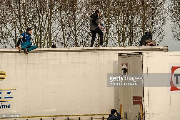 Migrant or refugees enters the trailer of a truck after having cut the tarpaulin roof on December 17 2015 on the site of the Eurotunnel in Calais A...