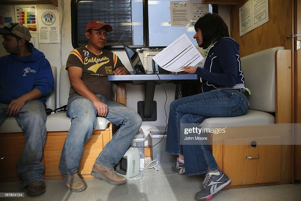 Migrant outreach coordinator Jessica Perez del Olmo speaks with an immigrant farm worker from Mexico before giving him a physical examination on April 30, 2013 in Brighton, Colorado. Salud family Health Centers sends a mobile clinic to farms throughout northeastern Colorado to serve the migrant population, many of whom ave little access to health care, which has become a major issue in health care reform proposals.