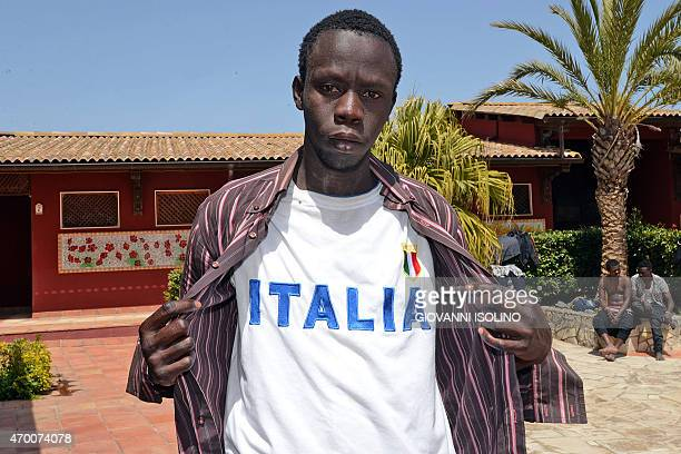 A migrant poses with a teashirt reading 'Italia' at the Oasi Don Bosco immigration center on April 17 2015 in Sicily The UN refugee agency said over...