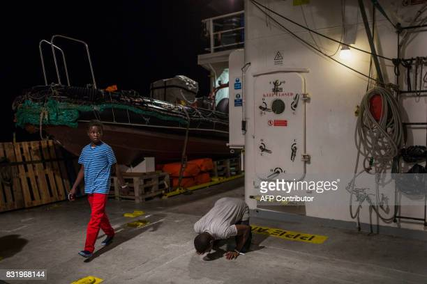 A migrant prays on the deck of the Aquarius rescue ship run by NGO SOS Mediterranee and Medecins Sans Frontieres after his transfer from the NGO...