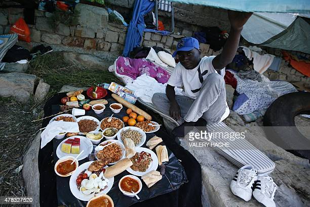 A migrant prepares to break his fast with the 'iftar' meal during the Muslim fasting month of Ramadan in the city of Ventimiglia on the FrenchItalian...