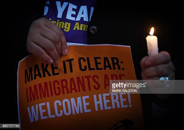 Migrant rights groups hold candles during a vigil to protest against US President Donald Trump's new crackdown on 'sanctuary cities' outside the City...