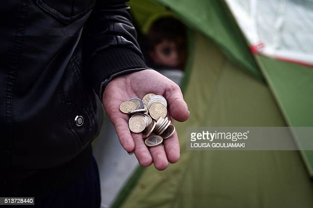 A migrant shows a handful of euro coins that he has left as refugees and migrants wait for food in a makeshift camp at the Greek Macedonian borders...