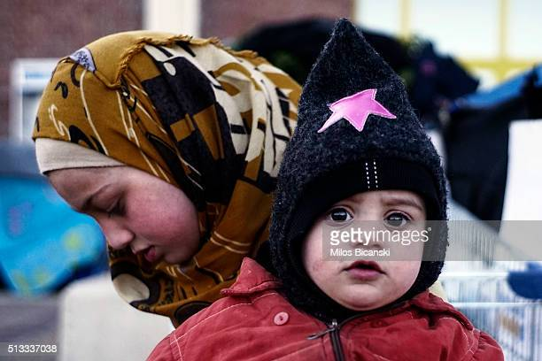 A migrant sister and brother from Syria outside a passenger terminal where migrants have found a shelter at the port of Piraeus on March 2 2016 in...