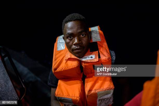 A migrant sits aboard a boat of run by of Aquarius rescue ship run by NGO SOS Mediterranee and Medecins Sans Frontieres after he was rescued by NGO...