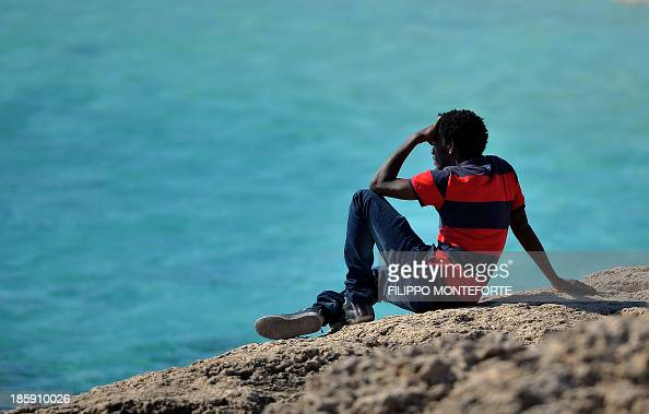 A migrant sits on rocks and stares at the sea in Lampedusa island on October 26 2013 There are currently three navy vessels on patrol along with six...