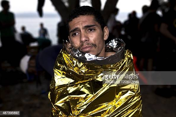 A migrant sits with a thermal blanket wrapped around himself upon his arrival on the shores of the Greek island of Lesbos after crossing the Aegean...