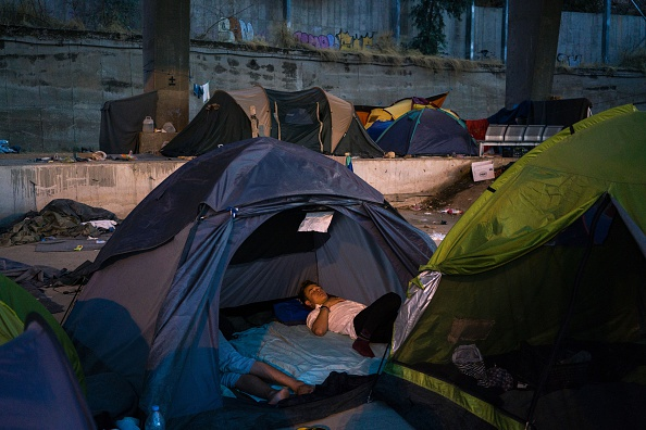 A migrant sleeps inside a tent in the port of Piraeus, where nearly 1,500 refugees and migrants live in a make-shift camp in Athens on July 17, 2016. In partnership with local aid groups Faros and ...