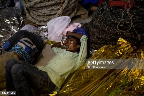 TOPSHOT A migrant sleeps on the deck of the Aquarius rescue ship run by NGO SOS Mediterranee and Medecins Sans Frontieres after his transfer from the...