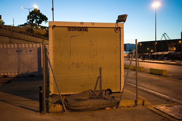 TOPSHOT - A migrant sleeps on the ground in the port of Piraeus, where nearly 1,500 refugees and migrants live in a make-shift camp in Athens on July 17, 2016. In partnership with local aid groups ...