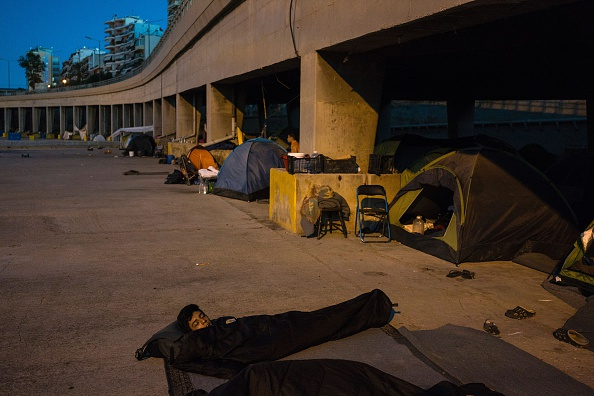 A migrant sleeps on the ground next to tents in the port of Piraeus, where nearly 1,500 refugees and migrants live in a make-shift camp in Athens on July 17, 2016. In partnership with local aid gro...